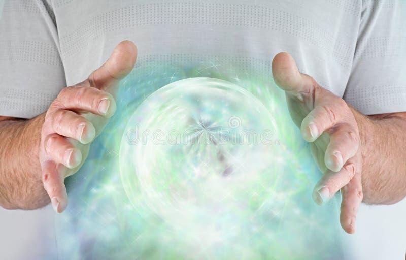 Mannetje met handen rond groene orb van hartchakra van energie royalty-vrije stock afbeelding