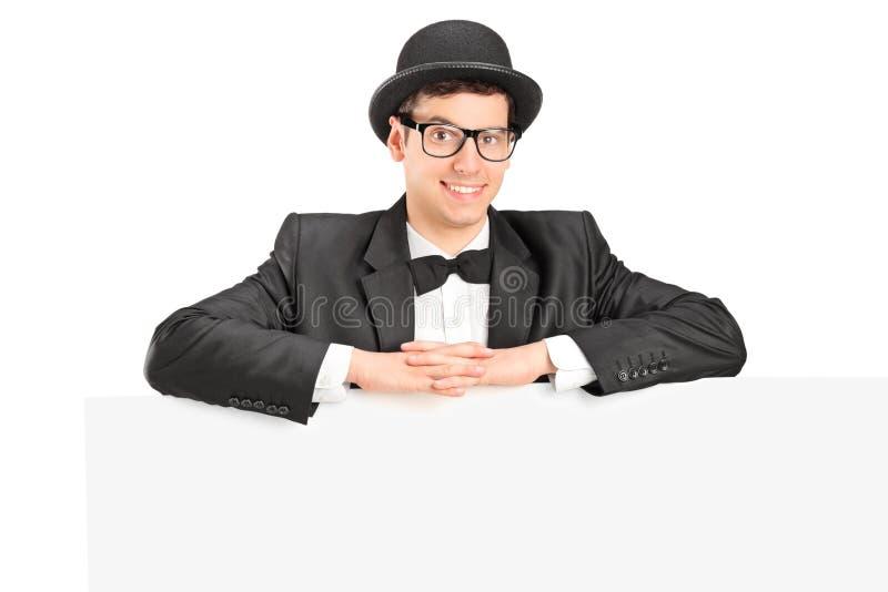 Mannetje met hoed en vlinderdas achter een paneel stock foto