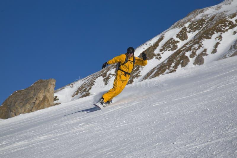 Mannetje op snowboard op de helling van berg royalty-vrije stock foto's