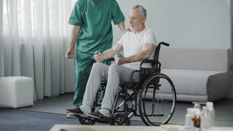 Mannetje in rolstoel die zijn zwakke spieren met hulp van verpleegster pompen, rehabilitatie royalty-vrije stock foto's
