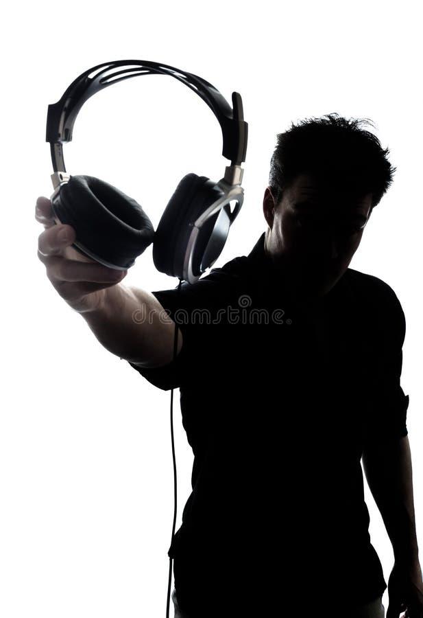 Mannetje in silhouet die hoofdtelefoons tonen stock foto's