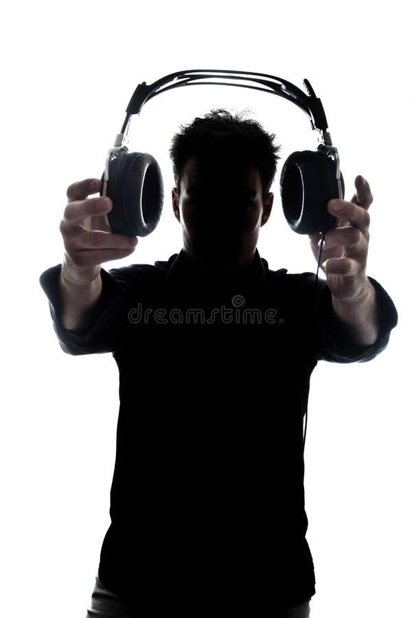 Mannetje in silhouet die hoofdtelefoons tonen stock afbeeldingen