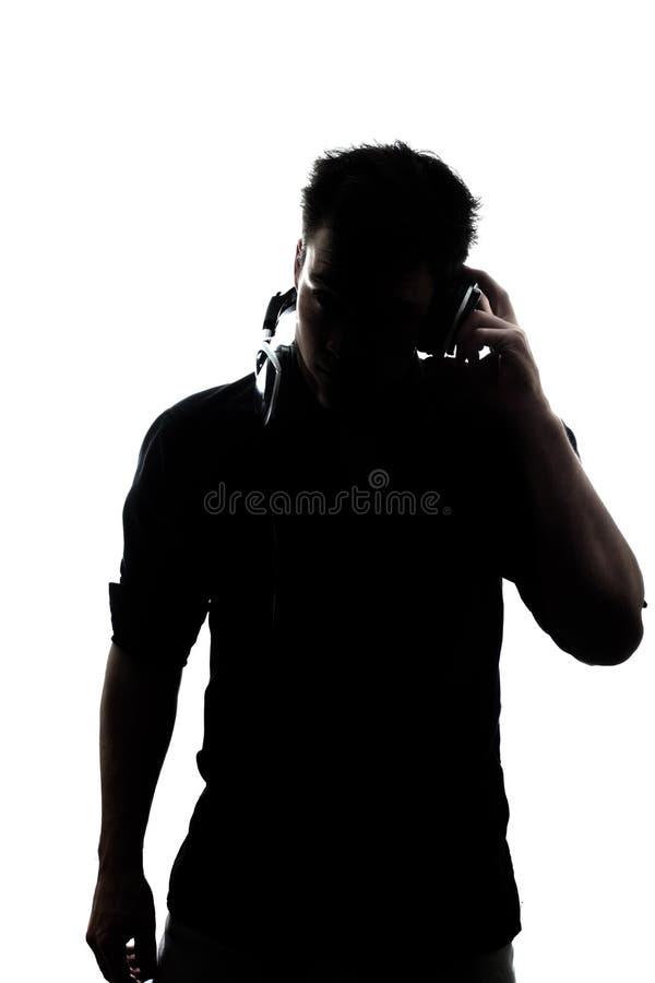 Mannetje die in silhouet aan hoofdtelefoons luisteren royalty-vrije stock fotografie