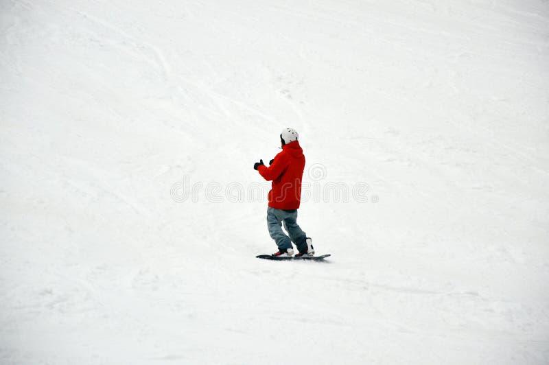 Mannetje snowboarder met raad die op sneeuw zich bergaf in Bukovel bevinden royalty-vrije stock afbeeldingen