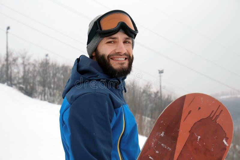 Mannetje snowboarder op helling bij de wintertoevlucht stock fotografie