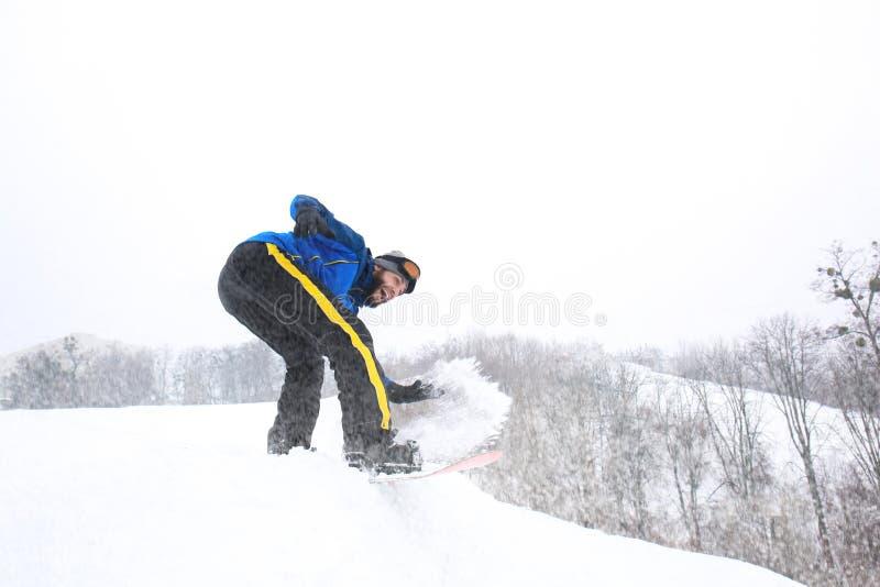 Mannetje snowboarder op helling bij de wintertoevlucht stock afbeelding