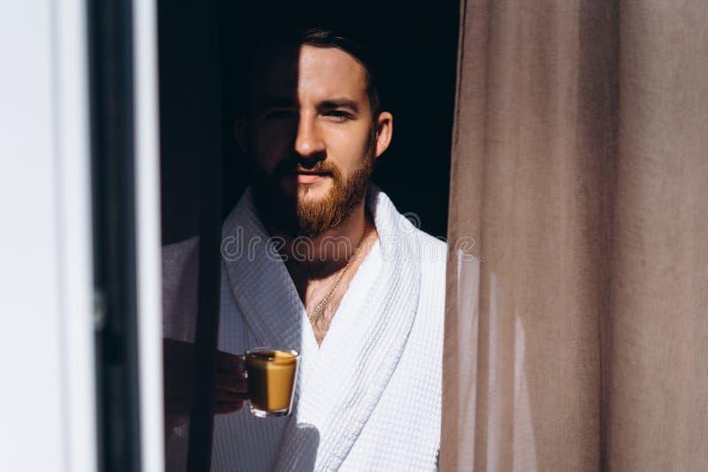 Mannetje in witte badjas met koffiemok ter beschikking stock fotografie