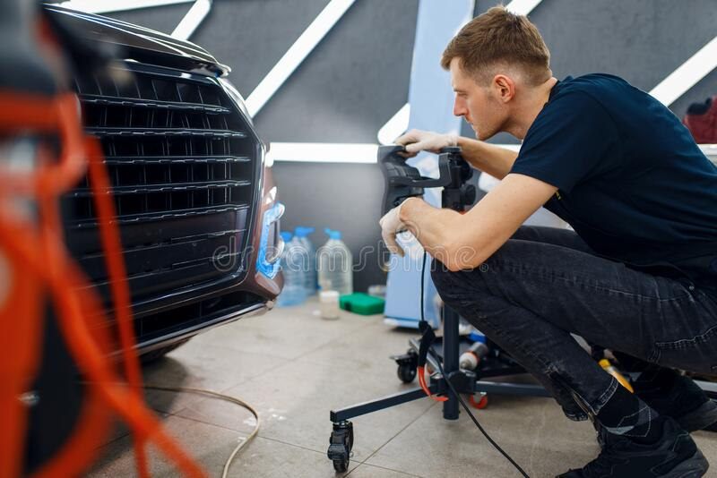 Mannetwerker rijdt auto-beschermingsfilm, auto-afstelling royalty-vrije stock foto's