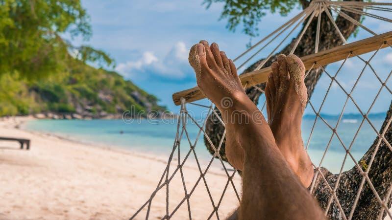 Mannfüße in der Hängematte, entspannend auf dem Strand in Haad Rin, Ko Phangan stockbilder