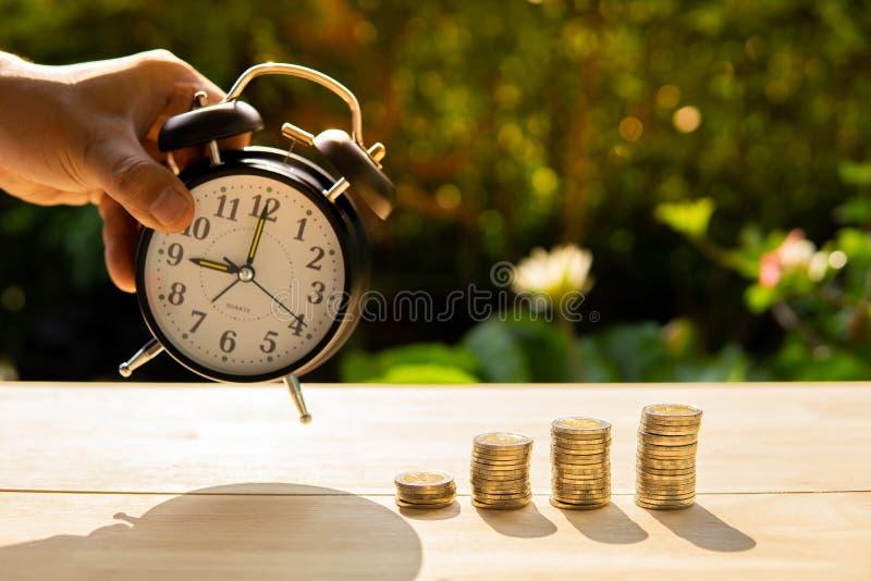 Mannfangwecker und der Geldmünzenstangenstapel auf hölzernem Tabellen- und Sonnenunterganghintergrund in den Showeinsparungen des stockbilder
