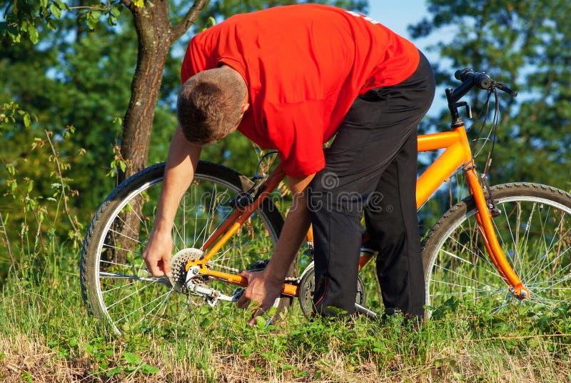 Mannfestlegungswanze auf Fahrrad lizenzfreie stockbilder