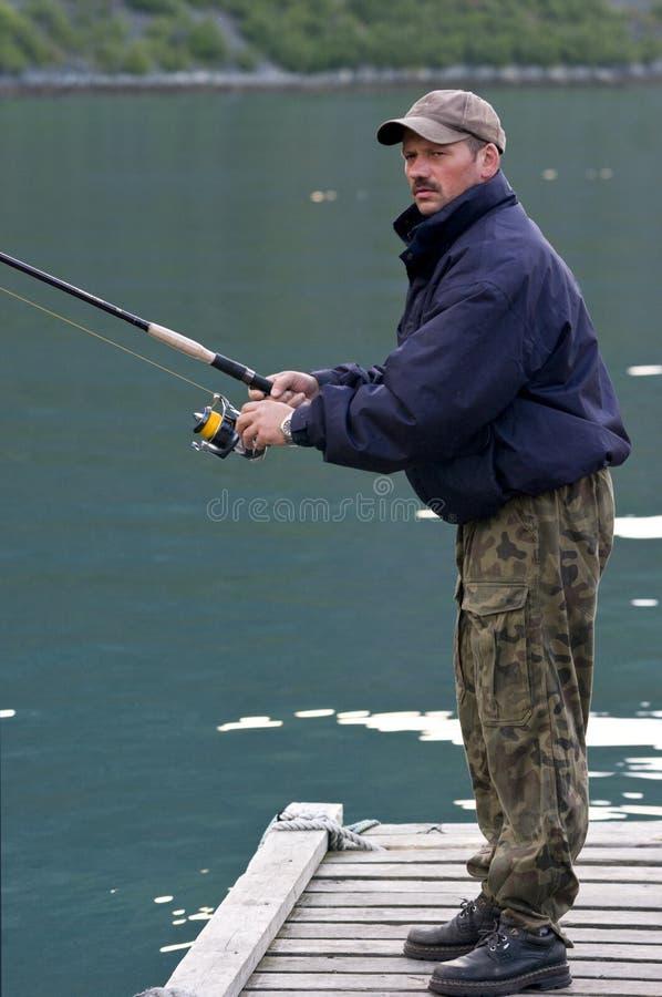 Mannfischen auf Anlegestelle lizenzfreie stockbilder