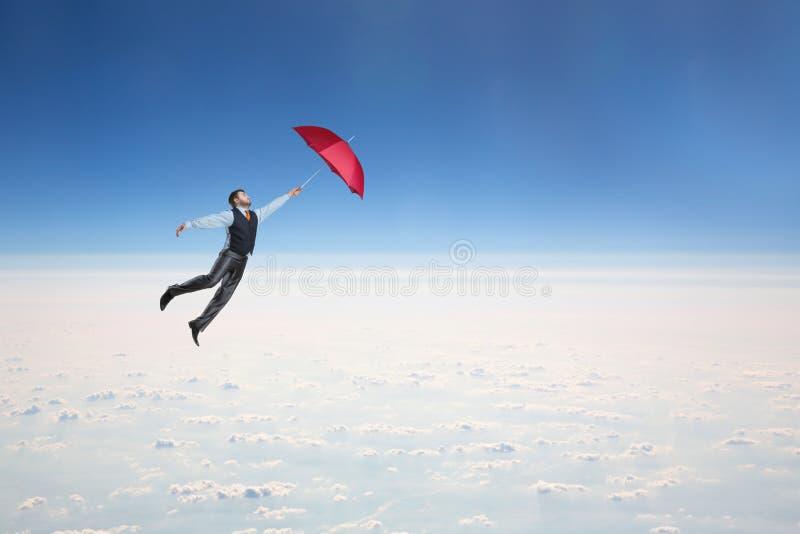 Mannfliegen im Himmel mit Regenschirm lizenzfreies stockbild