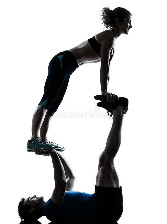 Mannfrau, die akrobatisches Trainingseignungsschattenbild ausübt stockfotografie