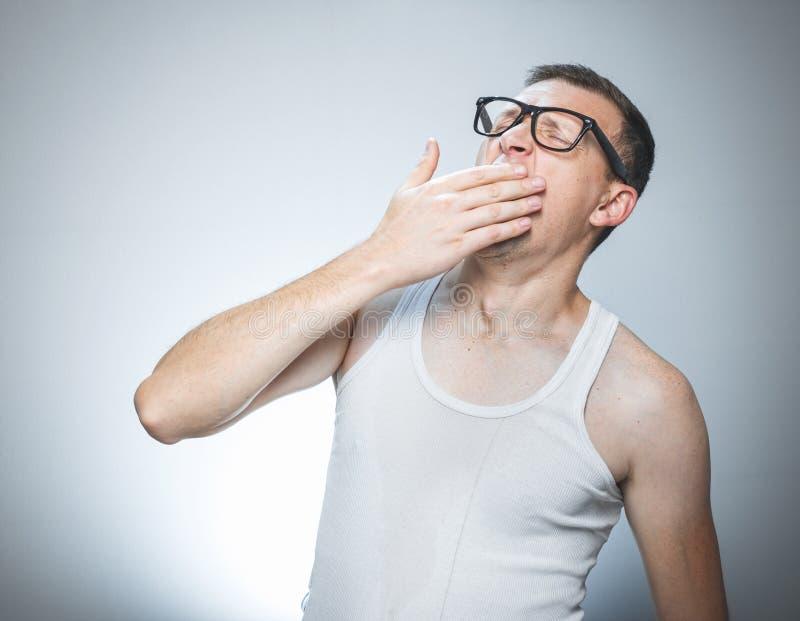 Manngähnen, weckend lizenzfreie stockfotografie