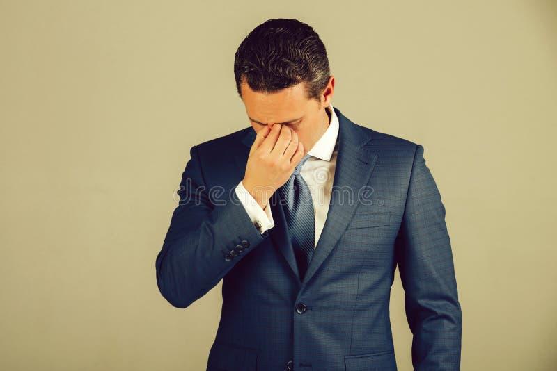 Manngefühlskopfschmerzen in der blauen Klage lizenzfreie stockbilder