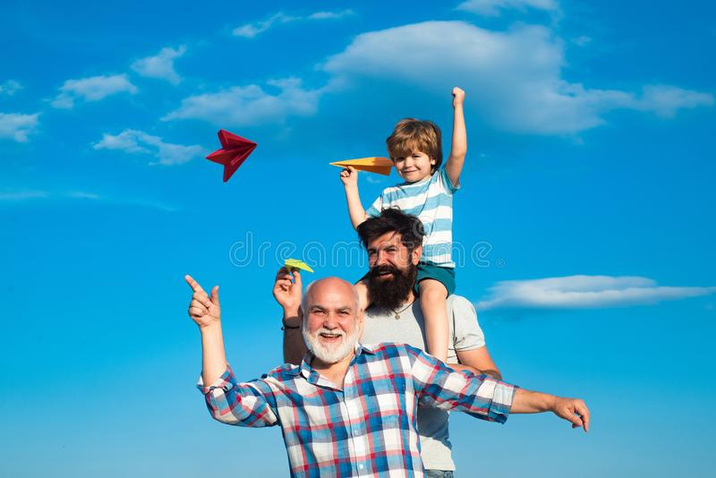 Manngeneration: großväterlicher Vater und Enkel umarmen, Kamera und das Lächeln betrachtend Vater- und Sohngenie?en stockfotos