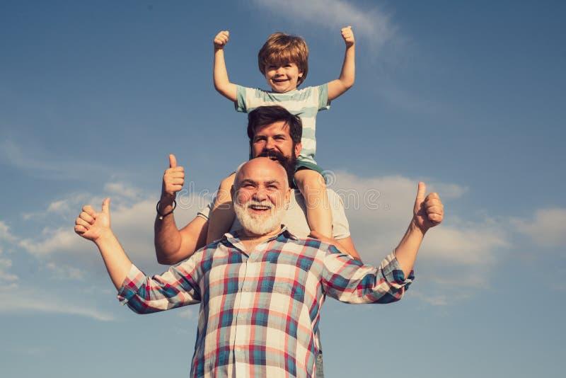 Manngeneration Vater und Sohn mit Großvater - glückliche liebevolle Familie Nettes Kind, das seinen Vater und Großvater umarmt stockbild