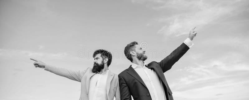 Manngesellschaftsanzugmanager, die auf entgegengesetzte Richtungen zeigen Ändernder Kurs Neue Geschäftsrichtungen Sich entwickeln lizenzfreies stockfoto