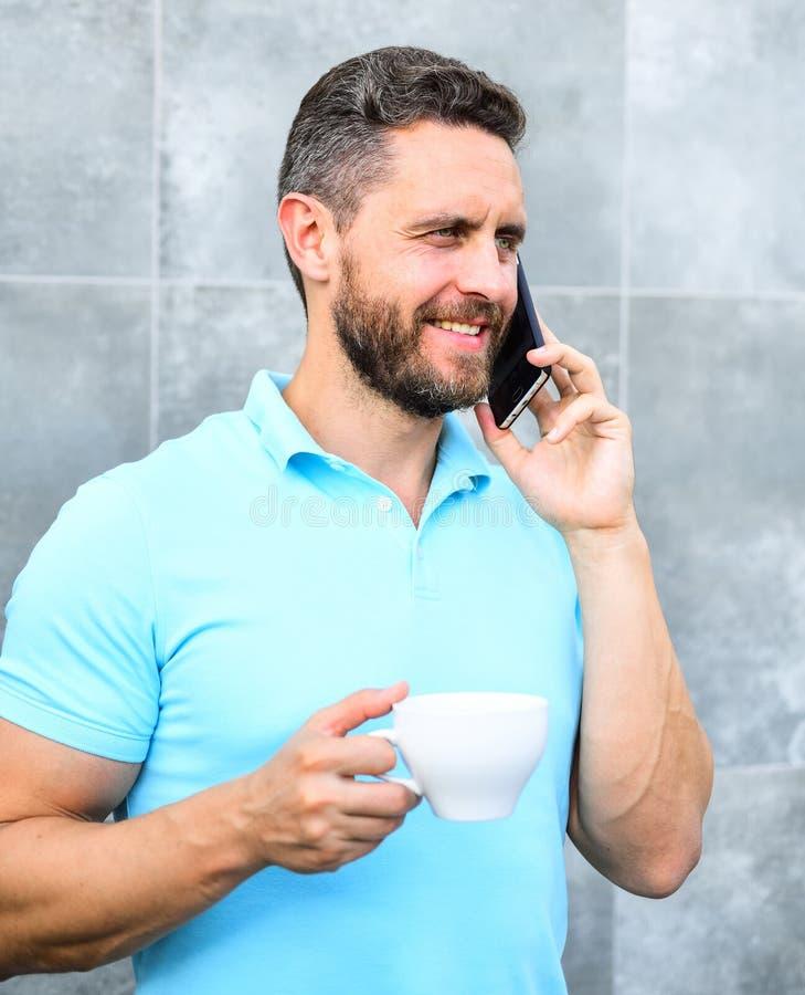 Manngetränkcappuccino sprechen grauen Wandhintergrund des Telefons Kaffee kann endlos reimagined machen etwas altes neues wieder lizenzfreies stockbild