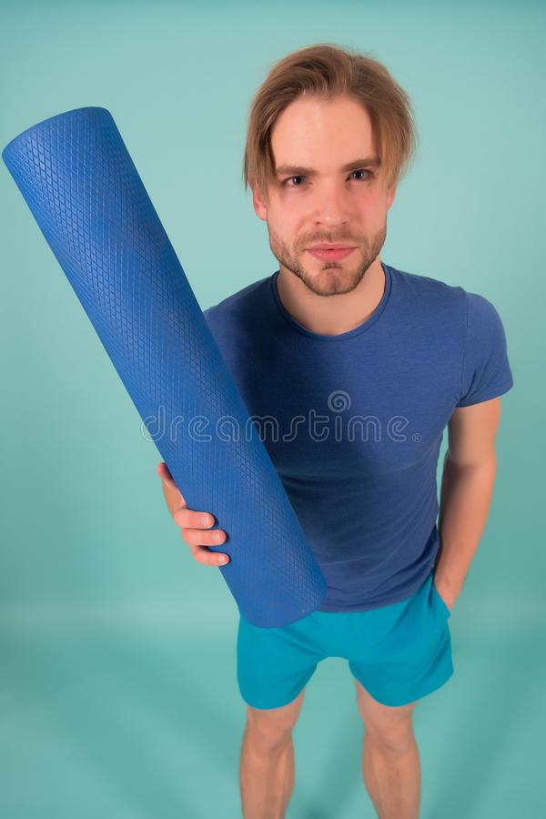 Manngriff-Yogamatte Modeathlet im blauen T-Shirt und in den kurzen Hosen Sportler mit stilvollen Borste und dem Haar Turnhallenau stockfotos