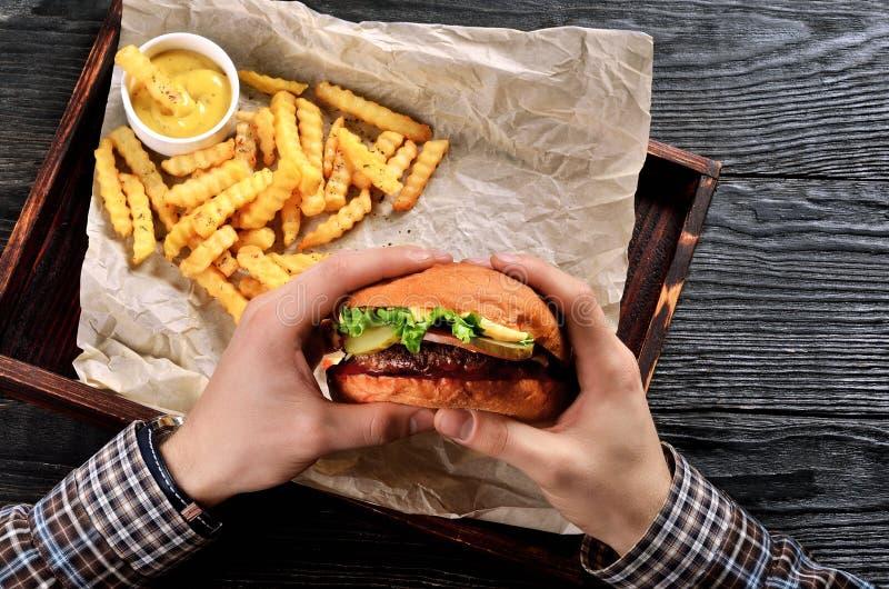 Manngriffburger in den Händen lizenzfreie stockbilder