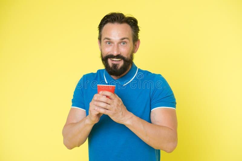 Manngriffpapier-Kaffeetasse des Hippies stehen reife gelben Hintergrund Entspannende Kaffeepause Trinken Sie es unterwegs Mann bä stockbild