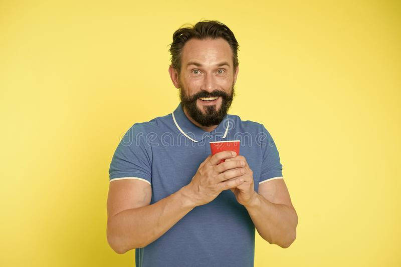 Manngriffpapier-Kaffeetasse des Hippies stehen reife gelben Hintergrund Entspannende Kaffeepause Trinken Sie es unterwegs Mann b? lizenzfreie stockbilder