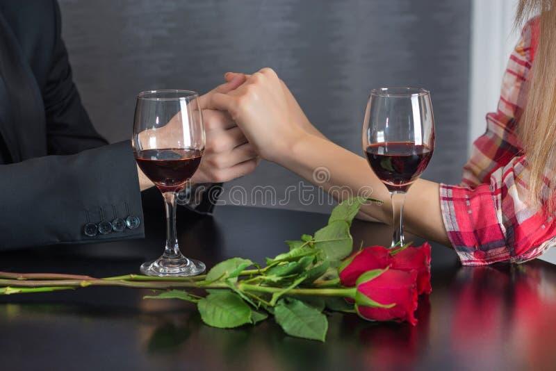 Mannhändchenhalten des Mädchens auf Restauranttabelle mit zwei Rotweingläsern und roten Rosen blüht stockfotografie