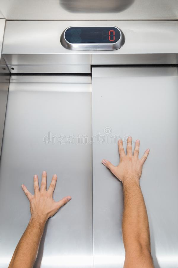 Mannhände auf Aufzugstür stockbild