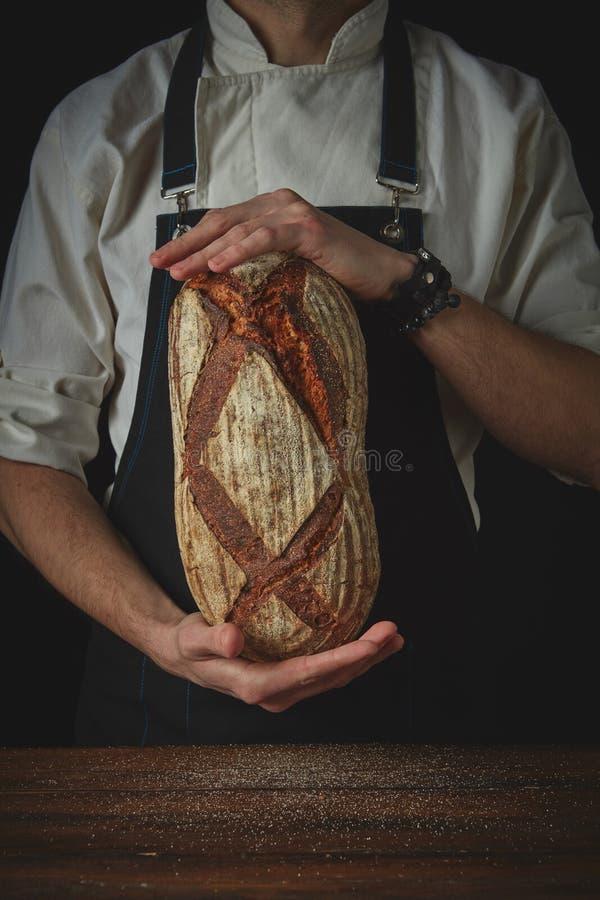 Mannhände, die ein ovales frisches Brot halten lizenzfreies stockbild