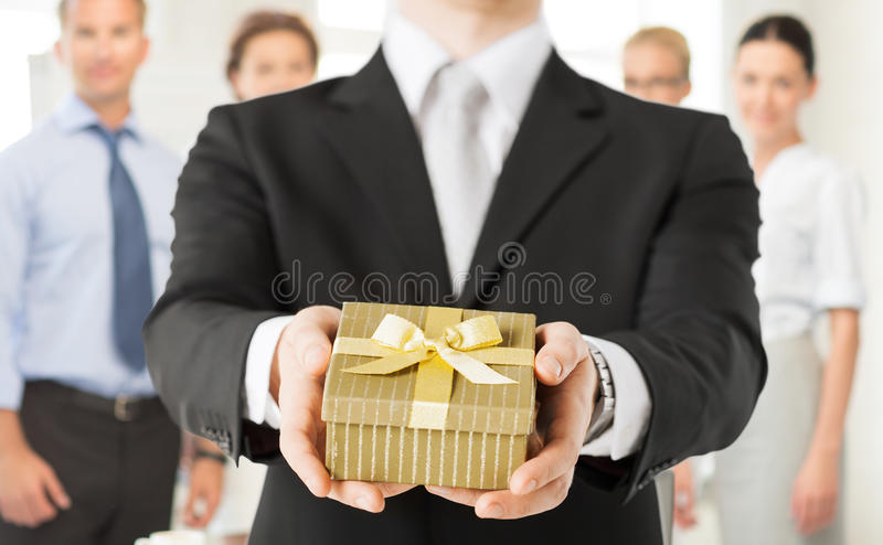 Mannhände, die Geschenkbox im Büro halten stockbilder