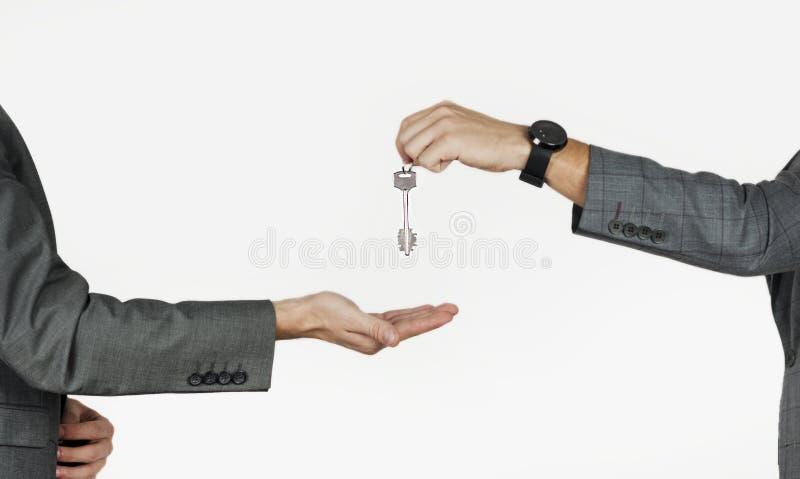 Mannhände, die Hausschlüssel, Wohnungen, Autos auf lokalisiert überreichen lizenzfreie stockbilder