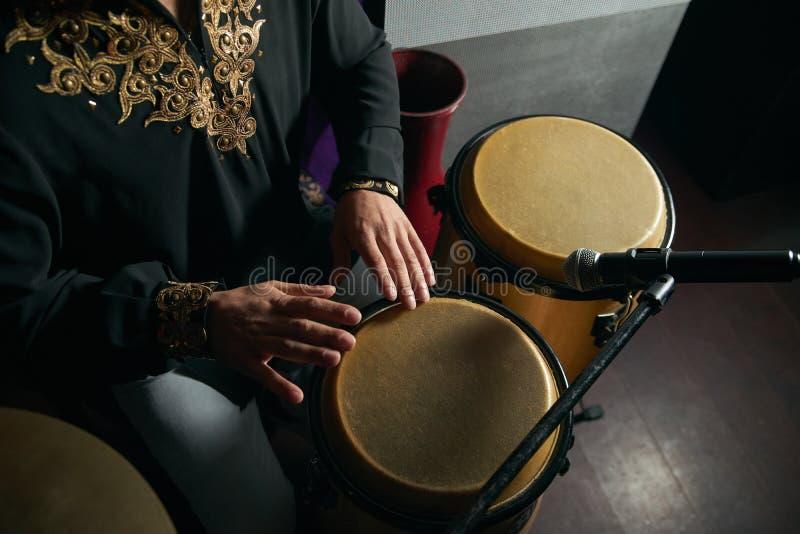 Mannhände, die Musik an djembe Trommeln spielen lizenzfreie stockfotografie