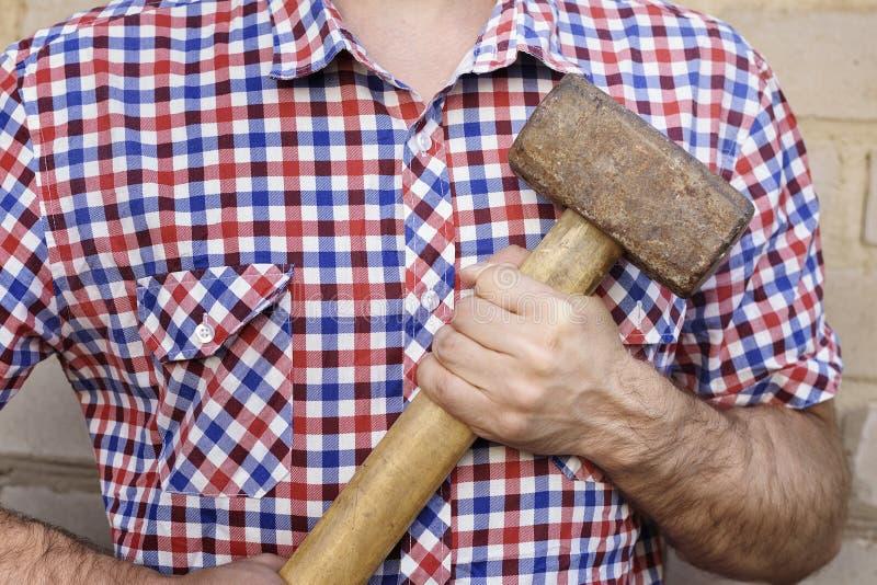Mannhände mit einem Hammer, auf dem Backsteinmauerhintergrund Arbeitsc stockfoto
