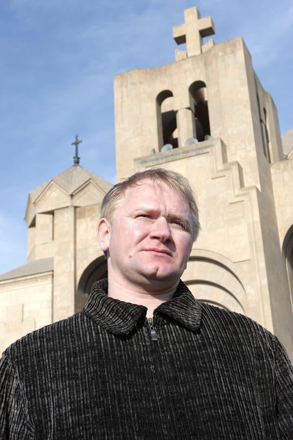 Mannhaltungen auf Kirchehintergrund lizenzfreies stockbild