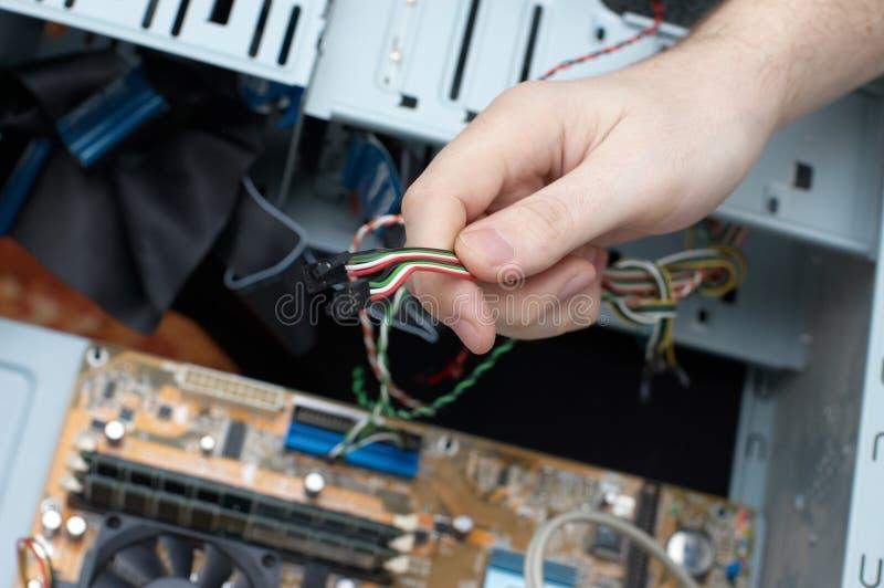 Mannhand baut Computerseilzug zusammen stockbild