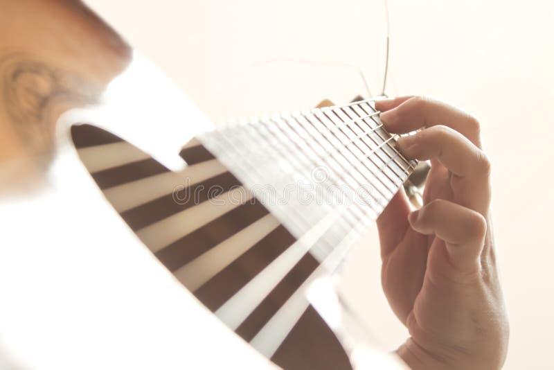 Mannhand, die auf Gitarre spielt stockfoto