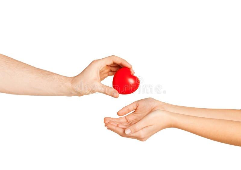 Mannhand, die der Frau rotes Herz gibt stockfoto