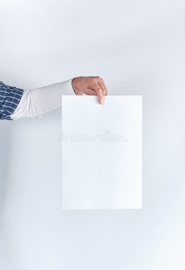 Mannhand, die ein rechteckiges Weißbuchblatt des freien Raumes hält stockfotos