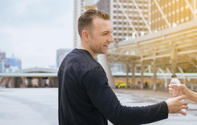 Mannhand, die Flasche Trinkwasser nach laufender Übung an der Hauptstadt gibt lizenzfreie stockfotos