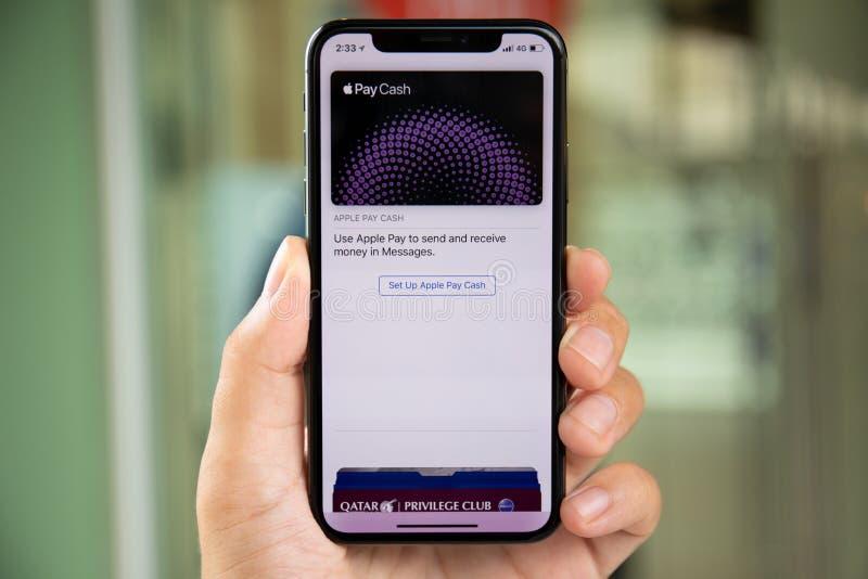 Mannhand, die iPhone X mit Apple-Lohn-Bargeld hält lizenzfreie stockbilder