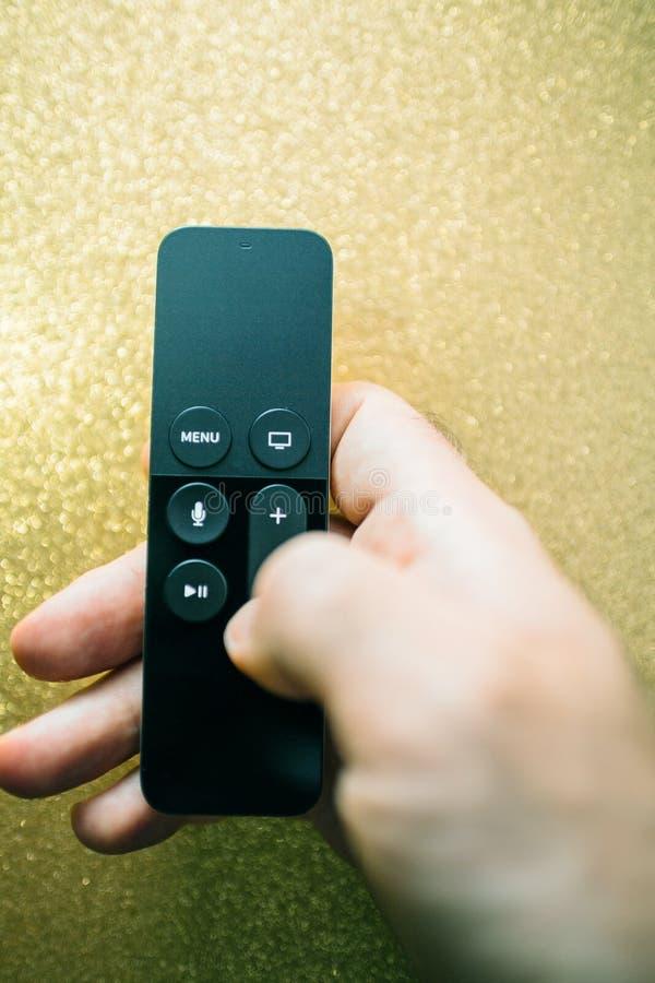 Mannhand, die moderne Spielerdirektübertragung Apple Fernsehen 4k hält stockbilder