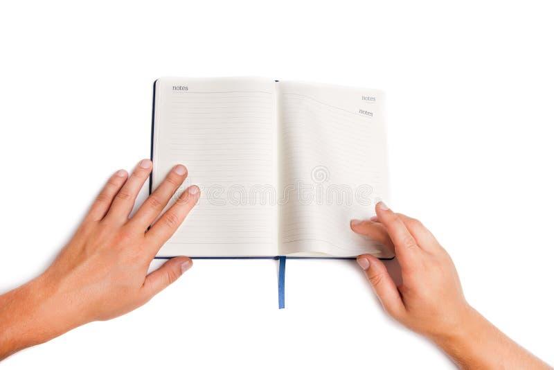 Mannhand, die offenes Buch auf Weiß hält stockfoto