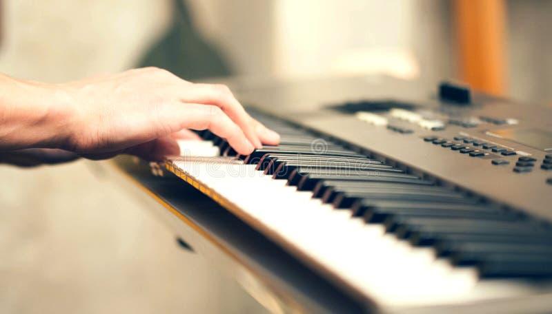 Mannhand, die zuhause musikalische Tastatur spielt lizenzfreie stockbilder