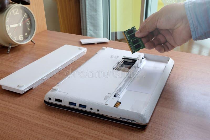 Mannhand halten änderndes RAM und Batterie für weiße Laptop-Computer auf Bretterboden lizenzfreie stockfotografie