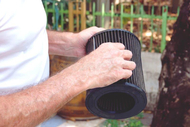 Mannhand mit dem Autoluftfilter, der Automotor überprüft stockfotografie