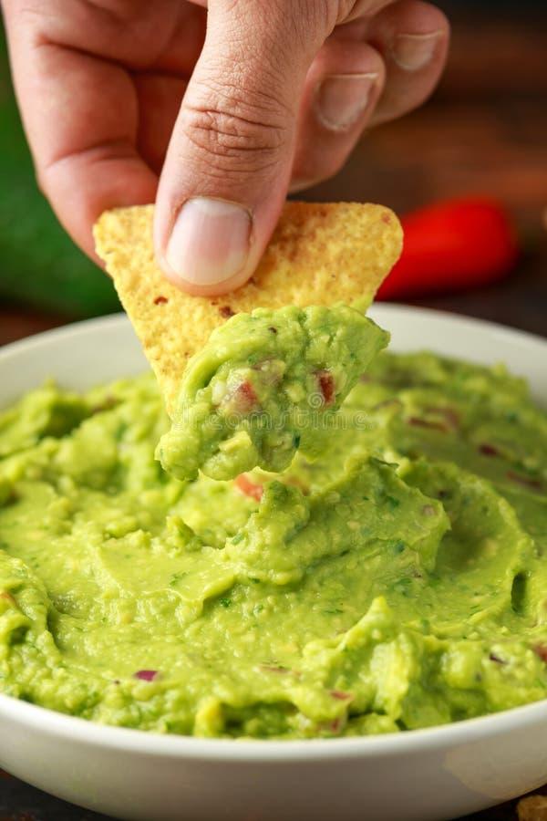 Mannhand wählt irgendein Guacamolebad mit Nachos abbrechen aus Gesunder strenger Vegetarier, Gemüsenahrung stockbilder