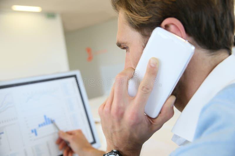 Mannhandelsaktien am Telefon stockbild
