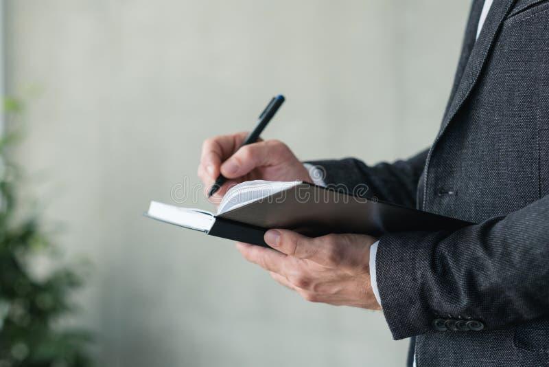 Mannhandschriftnotizbuch-Unternehmensplanungstagesordnung lizenzfreie stockfotografie